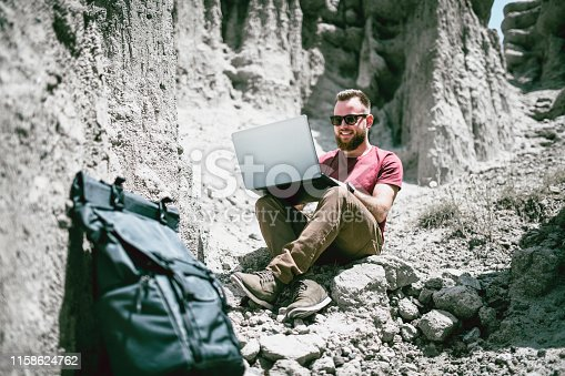 Happy Male Explorer Writing An Article About His Adventures On Laptop