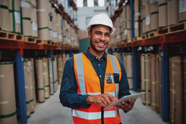 szczęśliwy mężczyzna kierownik fabryki za pomocą cyfrowego tabletu w magazynie, stojąc przed półką towarów patrząc na aparat - kask ochronny odzież ochronna zdjęcia i obrazy z banku zdjęć