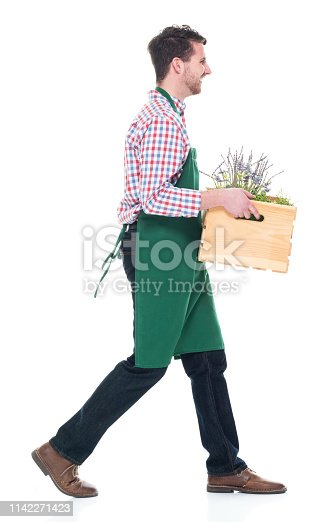 Happy male florist holding a basket with plants and walking