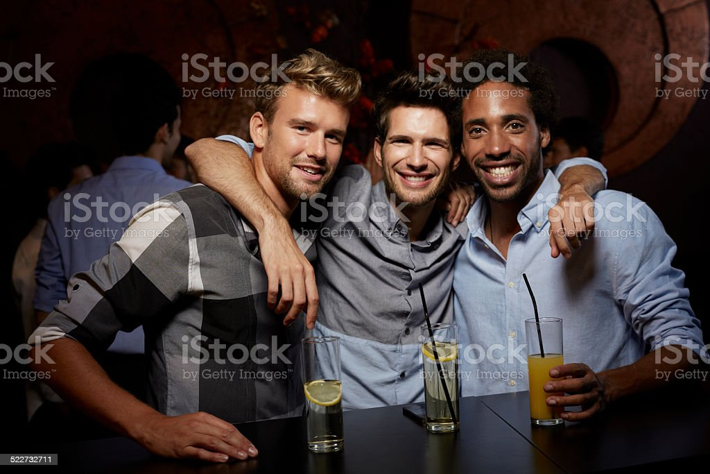 Happy male friends with drinks at nightclub stock photo