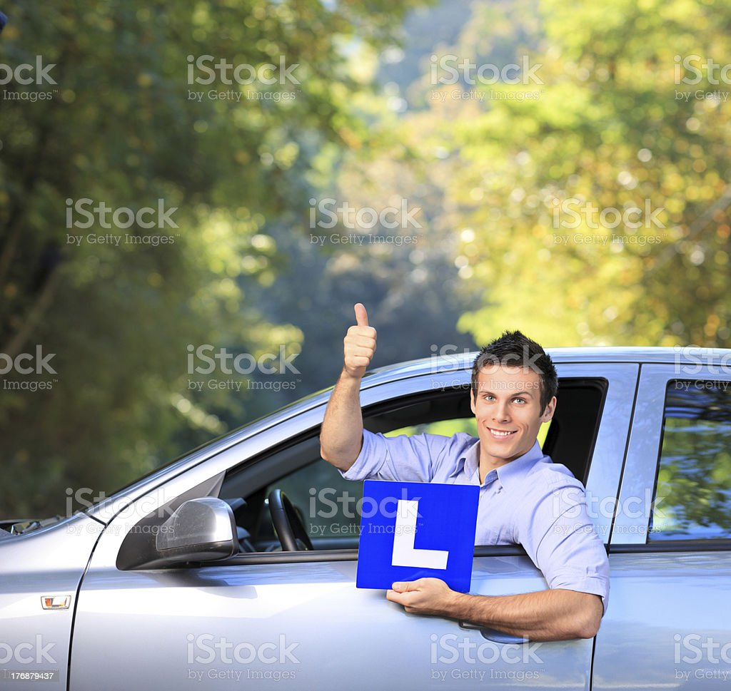 Happy male holding a L sign and giving thumb up stock photo
