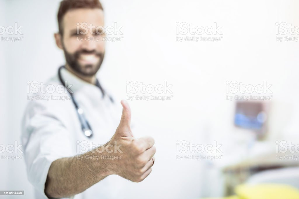 Happy male mid adult healthcare worker showing thumbs up. stock photo