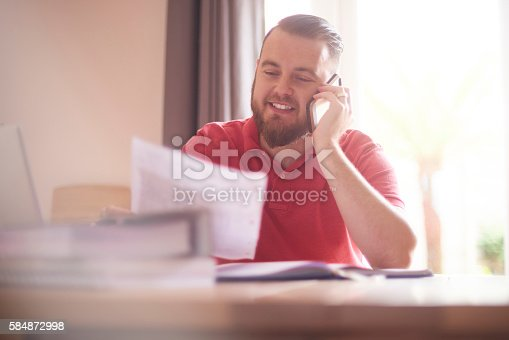 A young male possibly a single parent or small business owner sits at home talking to the bank or finance company on the phone. He is paying off his remaining debt and is feeling very happy about it. He is smiling as he listens to the advisor.