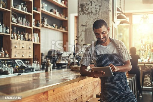 Portrait of professional barista standing at the counter of the coffee shop using digital tablet