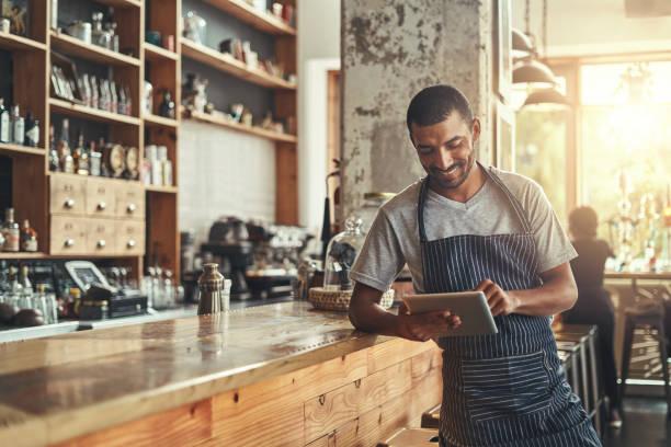 feliz dueño masculino de café usando tableta digital - restaurante fotografías e imágenes de stock