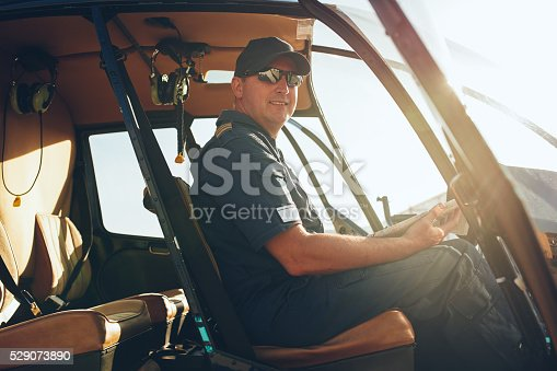 Portrait of happy male pilot sitting in the cockpit of a helicopter with a aviation map.