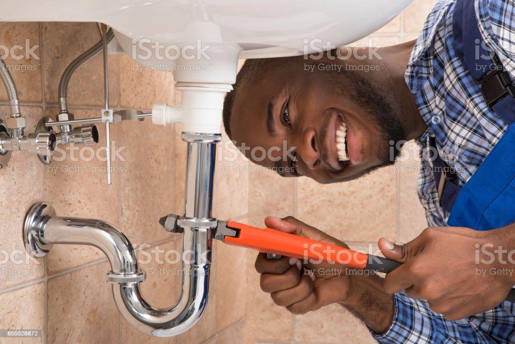 Happy Male Plumber Repairing Sink In Bathroom stock photo