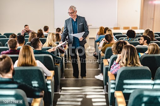 Happy senior professor talking to his students while giving them test results in lecture hall.