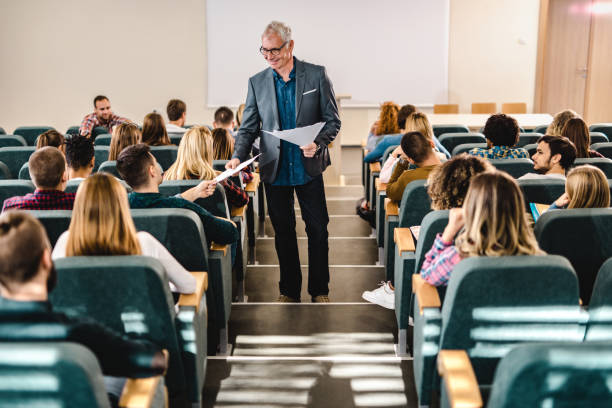 Happy male professor giving his students test results in amphitheater. stock photo