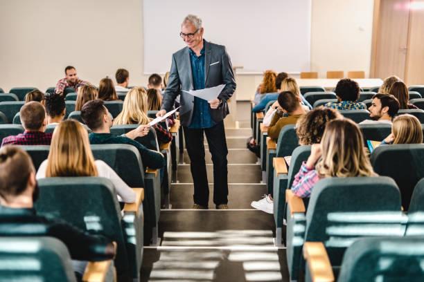happy male professor giving his students test results in amphitheater. - professore foto e immagini stock