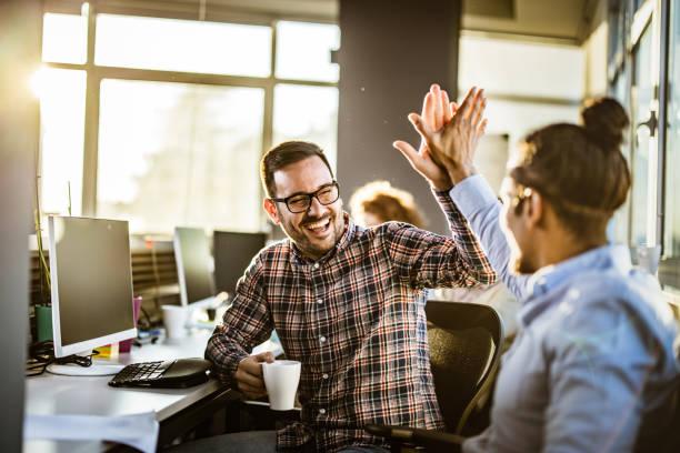 programadores masculinos felices que se dan el uno al otro alto-cinco en la oficina. - high five fotografías e imágenes de stock