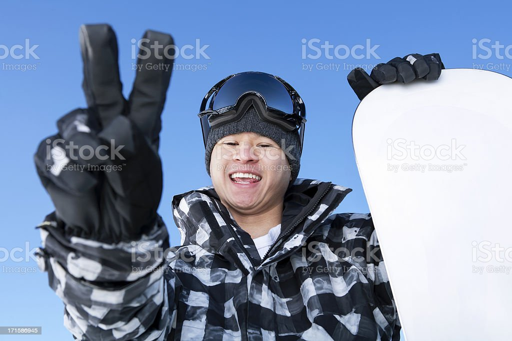 Happy male snowboarder with peace gesture against blue sky royalty-free stock photo