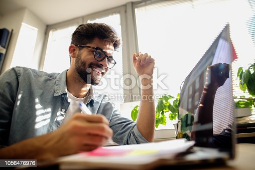 istock Happy male student learning for exam and using laptop while studying in library. 1056476976