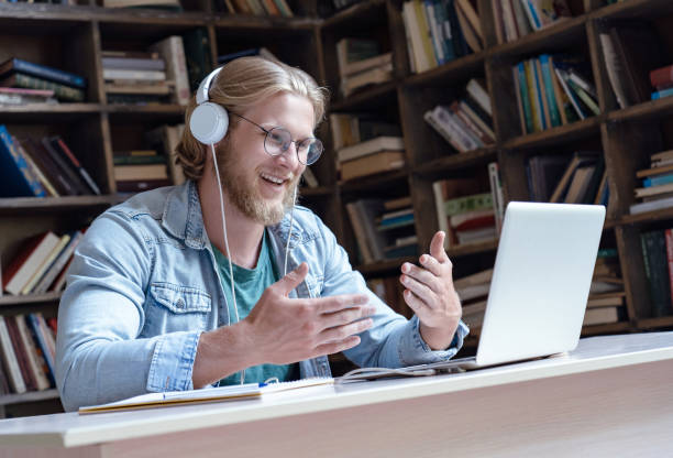 happy male student online teacher wear headphone talk video calling looking at laptop computer screen do conference chat communicate with skype tutor, distance education e learning course in library - skype imagens e fotografias de stock