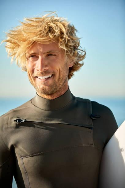 Glücklicher männlicher Surfer, der weg am Strand schaut – Foto