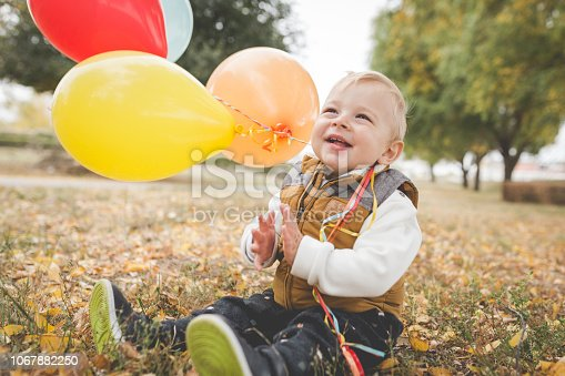istock Happy male toddler playing with balloons in the park 1067882250
