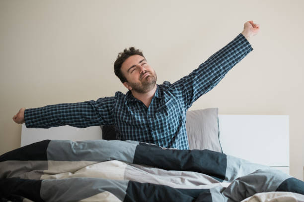 Happy male wake up and stretching arms stock photo