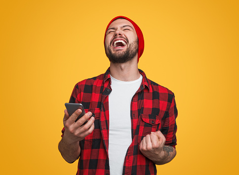 Handsome excited man in red beanie holding mobile phone and showing yes gesture with fist up standing on bright yellow studio background