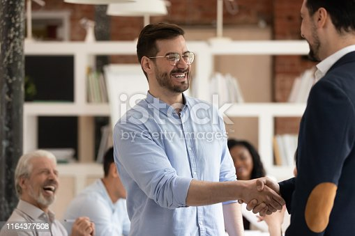 1070271598 istock photo Happy male worker get promoted rewarded handshake manager in office 1164377508