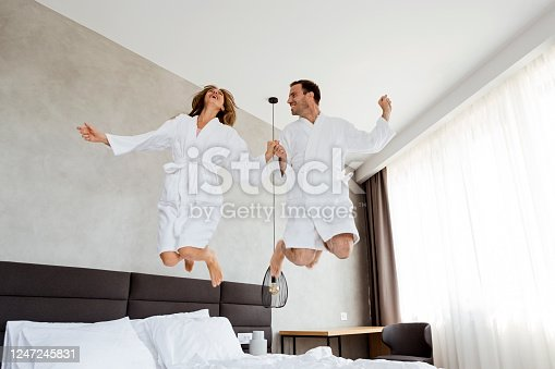 504371332 istock photo Happy man and a woman jumping on the bed 1247245831