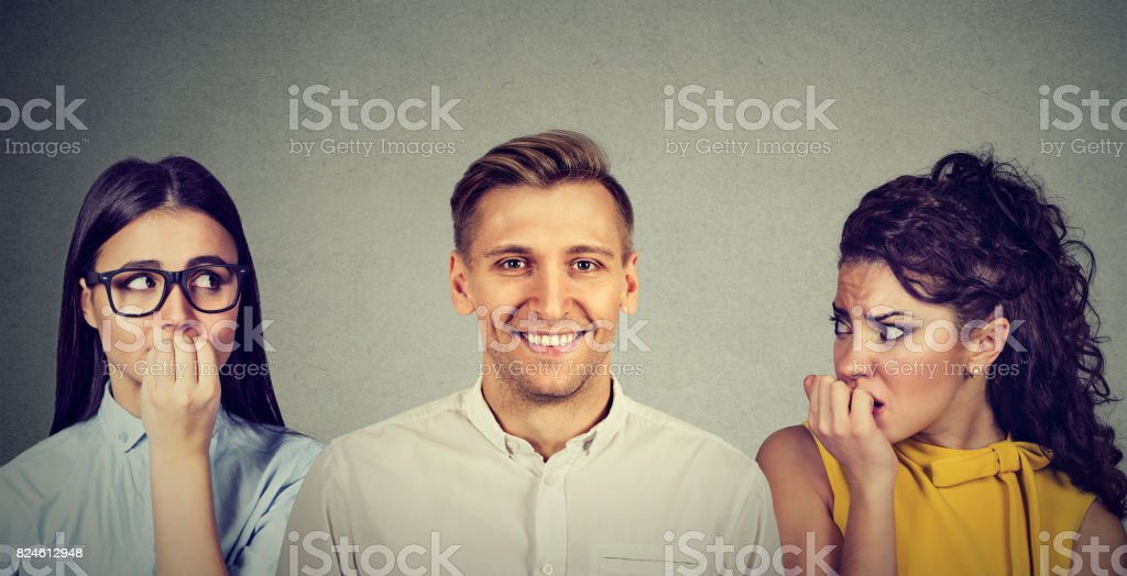 Happy man and two women anxiously looking at him stock photo