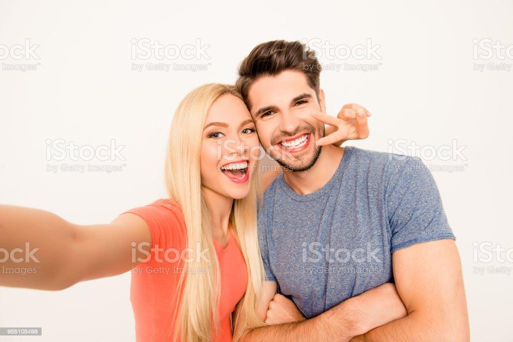 Feliz homem e mulher se divertindo e mostrando dois dedos durante a filmagem - foto de acervo