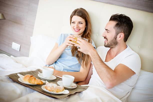 Glücklicher Mann und Frau mit Luxus-hotel mit Frühstück im Bett – Foto