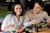 happy man and woman holding chopsticks with tasty sushi in restaurant