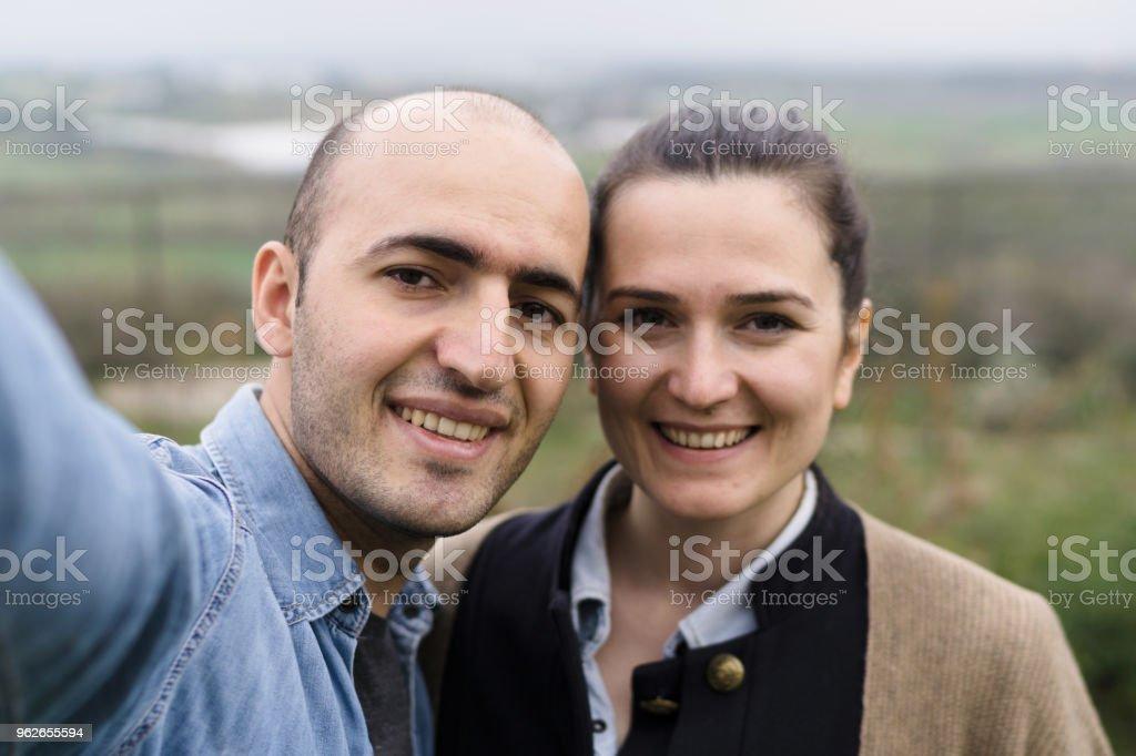 Happy man and woman in love making selfie