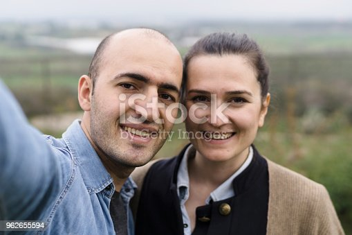 636831570 istock photo Happy man and woman in love making selfie 962655594