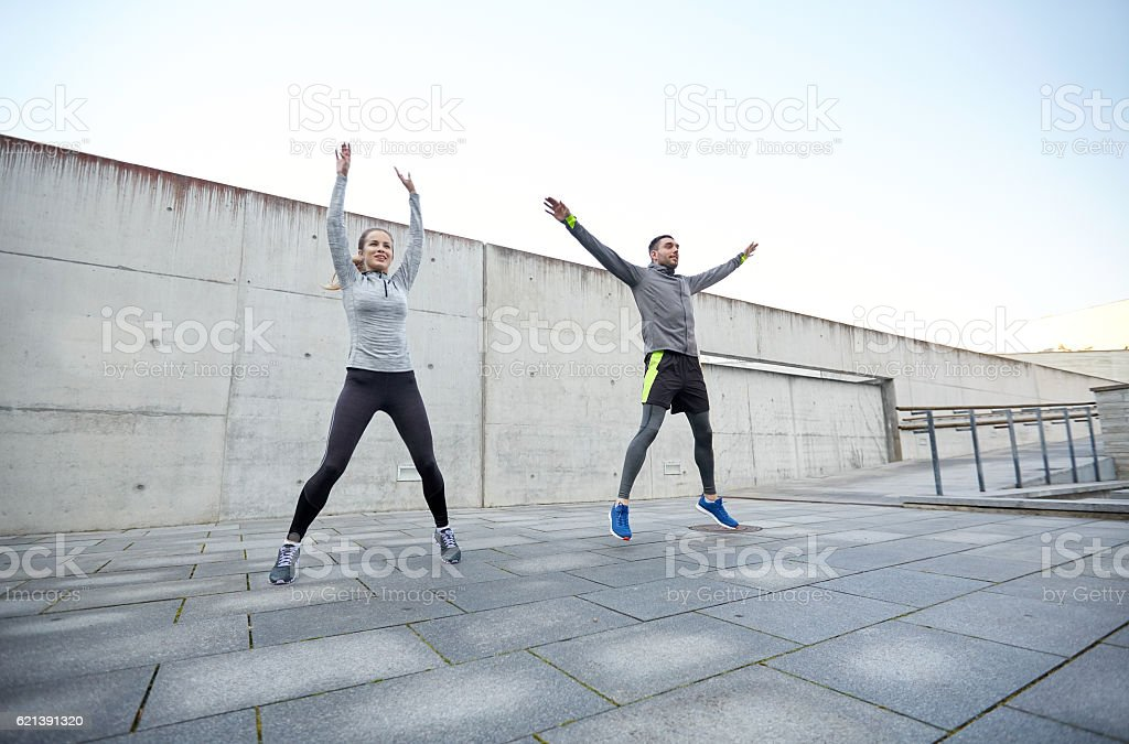 happy man and woman jumping outdoors - foto de stock