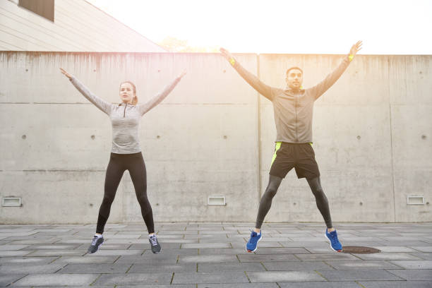 happy man and woman jumping outdoors stock photo