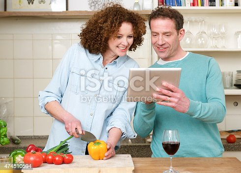 638771390istockphoto Happy man and woman looking at tablet in the kitchen 474510594