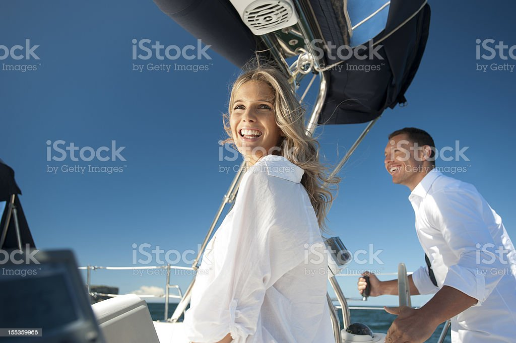 Happy man and woman on a sailboat stock photo
