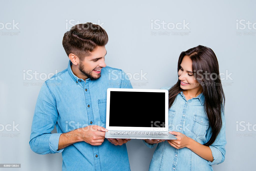Happy man and woman showing black screen of modern laptop stock photo