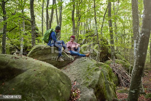Happy man and woman sitting on rock in forest. Mid adult hikers are talking while resting. They are enjoying autumn season in woodland.