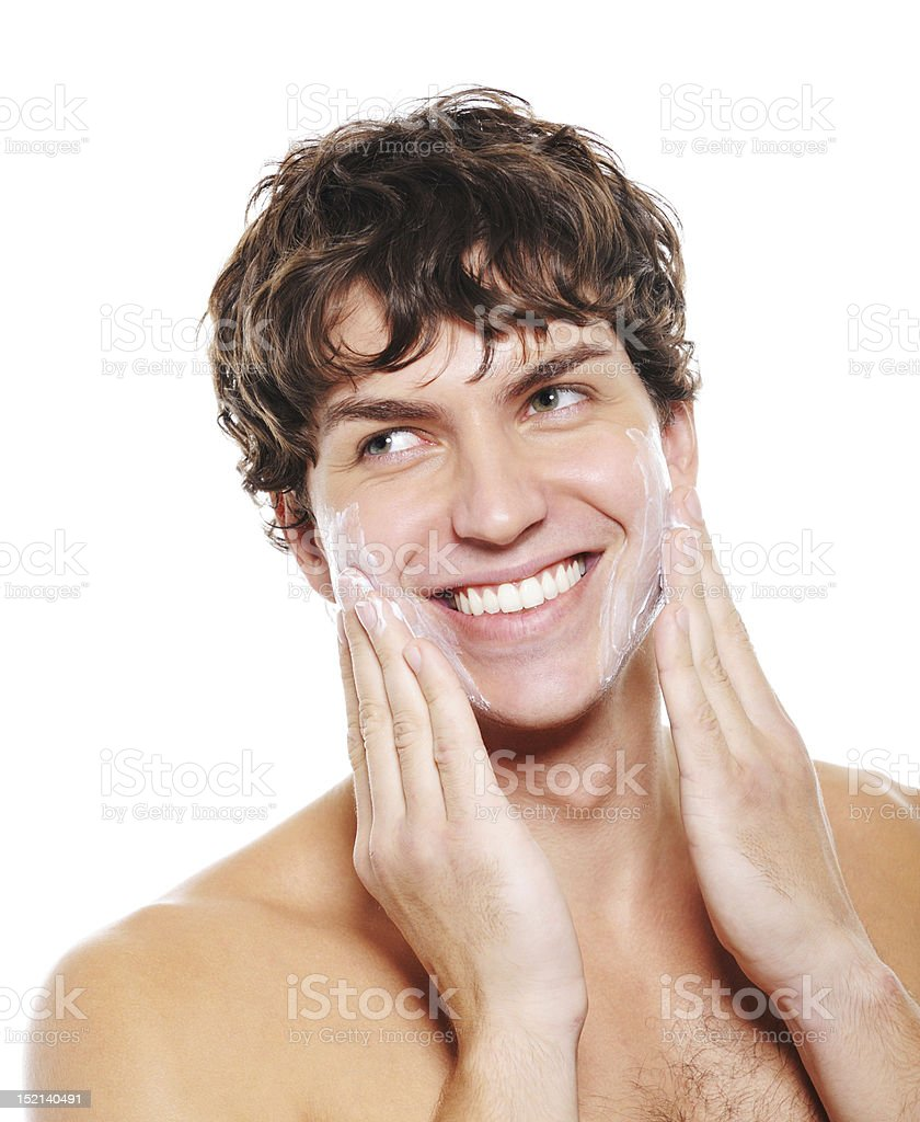 Happy man applying moisturizing cream after shaving royalty-free stock photo