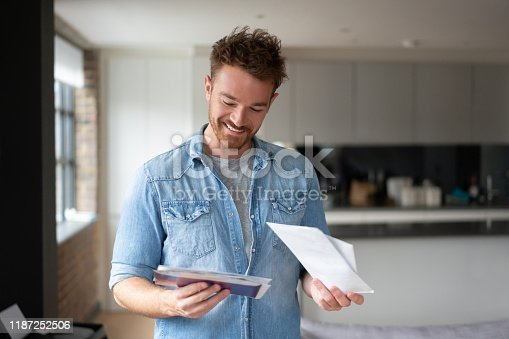 Portrait of a happy man at home checking the mail and smiling – lifestyle concepts