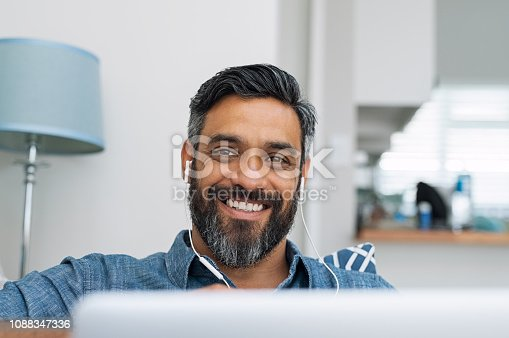 Portrait of happy man using laptop with earphones while lying on couch. Casual man in video call lying on sofa while listening to music with computer. Mature middle eastern man with earbuds looking at camera with a big smile.