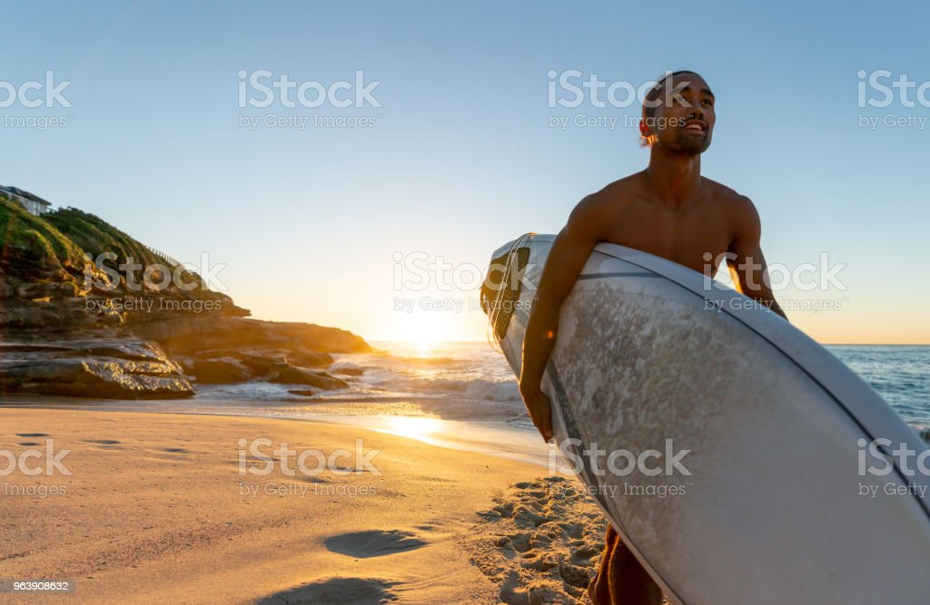 Happy man at the beach surfing and carrying his board - Royalty-free Adult Stock Photo