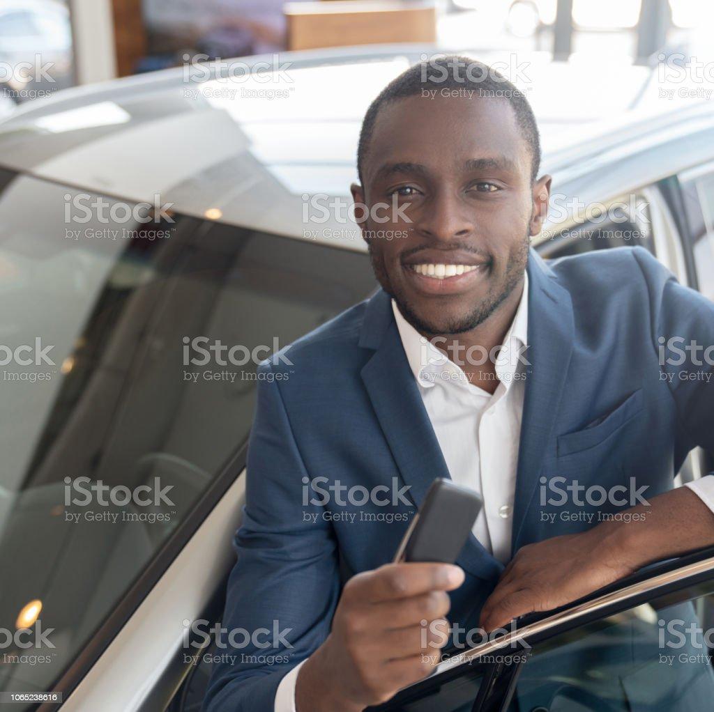 Happy man at the dealership holding keys to his new car stock photo