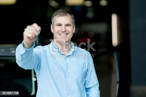 1138561232 istock photo Happy man at the dealership holding keys to his new car 824981738