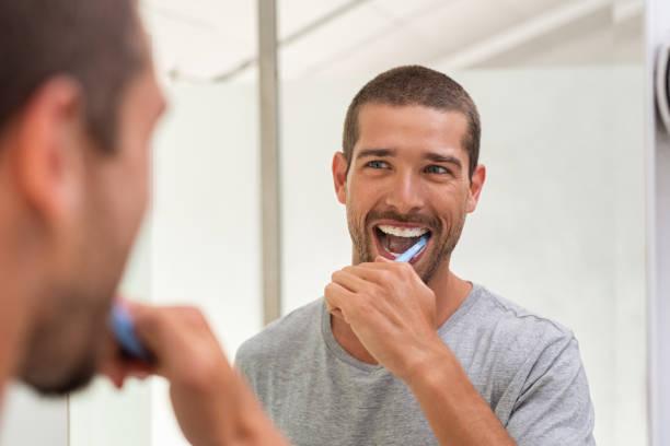 Happy man brushing teeth stock photo