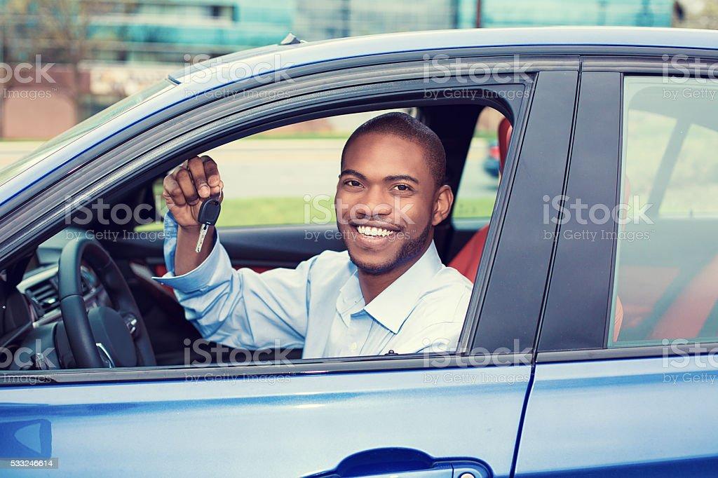 happy man, buyer sitting in new car showing keys stock photo