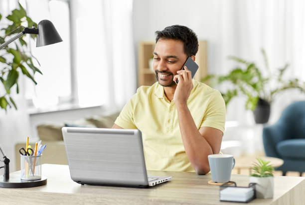 happy man calling on smartphone at home office stock photo
