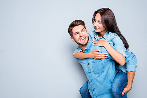 happy  man carrying his girlfriend on the back - boyfriend stock photos and pictures