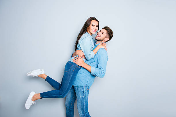happy man carrying his pretty wife on gray background - kinderjeans stock-fotos und bilder