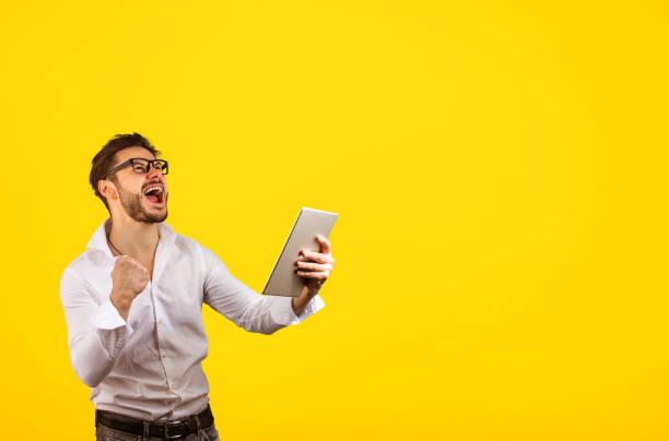 glücklicher mensch feiert sieg auf tablet - die besten apps stock-fotos und bilder
