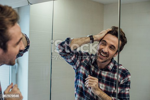 istock Happy man checking his mirror reflection 962929546