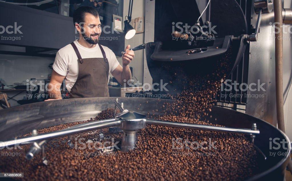Happy man checking preparing coffee grains stock photo